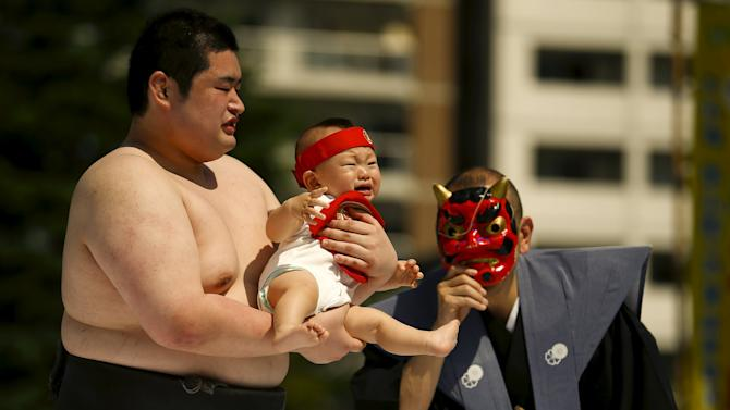 Ring assistant wears mask to scare baby held by amateur sumo wrestler during baby crying contest at Sensoji temple in Tokyo