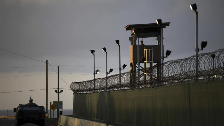 FILE – In this March 30, 2010, file photo reviewed by the U.S. military, a U.S. trooper stands in the turret of a vehicle with a machine gun, left, as a guard looks out from a tower at the detention facility of Guantanamo Bay U.S. Naval Base in Cuba. The Pentagon is asking Congress for more than $450 million for maintaining and upgrading the Guantanamo Bay prison that President Barack Obama wants to close. (AP Photo/Brennan Linsley, File)