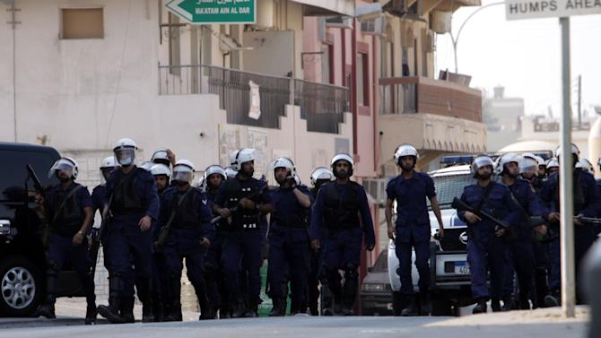 """Riot police enter the Shiite village of Jidhafs, Bahrain, on Friday, Sept. 23, 2011, where they chased protesters through narrow streets to keep them from heading into the capital of Manama. Bahrain's Sunni rulers are practicing """"fake democracy"""", the Gulf kingdom's leading Shiite cleric said Friday as opposition groups called for a boycott of weekend parliamentary elections and stepped up protests for greater rights. (AP Photo/Hasan Jamali)"""