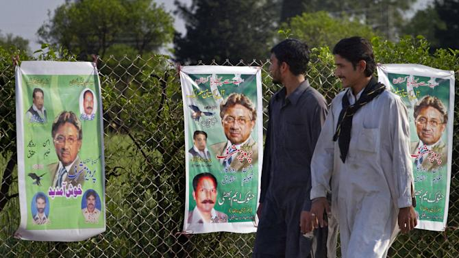 Pakistanis look at posters of former military ruler Gen. Pervez Musharraf along a roadside on the outskirts of Islamabad, Pakistan on Sunday, April 7, 2013. Musharraf was given approval on Sunday to run for parliament in a remote northern district after being rejected in two other parts of the country, his aide said. (AP Photo/Anjum Naveed)