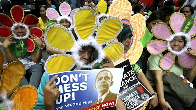 FILE - In this Nov. 14, 2012 file photo, protesters wearing flower costumes, display placards during a rally near the U.S. Embassy in Manila, Philippines to call on industrialized countries to act on the growing problem of climate change. Absent a magic potion or explosive economic growth, it was all but inevitable President Barack Obama would have to break some of his campaign promises to keep others, because of their incompatibility. Slowing the buildup of greenhouse gases responsible for warming the planet is one of the biggest challenges the U.S., and Obama faces. The impacts of rising global temperatures are widespread and costly: more severe storms, rising seas, species extinctions, and changes in weather patterns that will alter food production and the spread of disease. (AP Photo/Bullit Marquez, File)