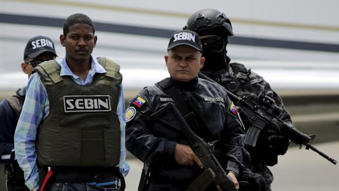 "Leiver Padilla Mendoza, alias ""El Colombia"", is escorted by police officers as he arrives to Venezuela, after being extradited from Colombia at Simon Bolivar Airport in Caracas"