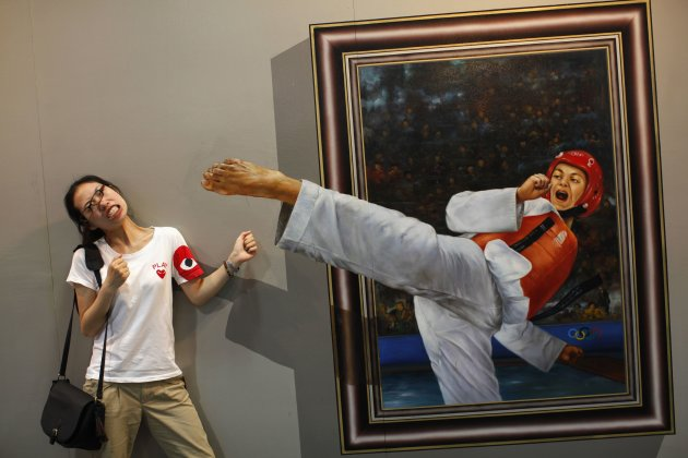 Woman poses for a photograph in front of a 3D painting at the 2012 Magic Art Special Exhibition in Hangzhou