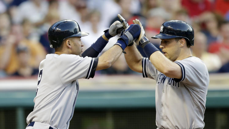 New York Yankees' Derek Jeter, left, congratulates Mark Teixeira after Teixeira hit a two-run home run off Cleveland Indians starting pitcher Josh Tomlin in the fifth inning of a baseball game Wednesday, July 9, 2014, in Cleveland. (AP Photo/Tony Dejak)