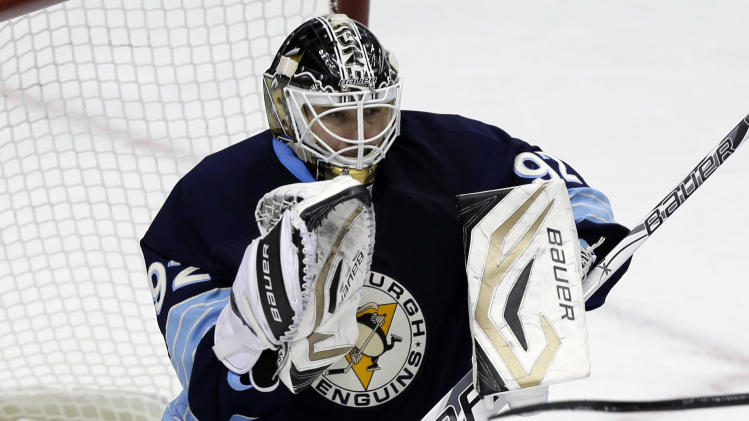 Pittsburgh Penguins goalie Tomas Vokoun (92) stops a shot in the first period of an NHL hockey game against the New York Islanders in Pittsburgh, Saturday, March 30, 2013. The Penguins won 2-0. (AP Photo/Gene J. Puskar)