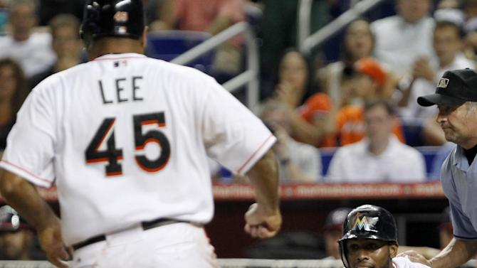 Miami Marlins' Jose Reyes yells to Carlos Lee (45) as he heads home during the third inning of a baseball game against the Washington Nationals, Tuesday, Aug. 28, 2012, in Miami. Both Reyes and Lee scored on a single by Greg Dobbs. (AP Photo/Wilfredo Lee)