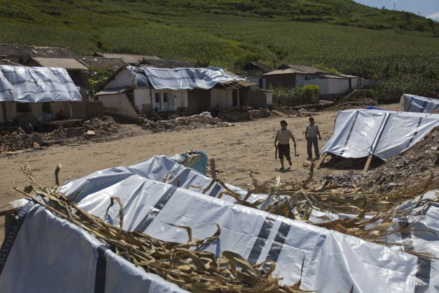 Displaced North Korean women, left homeless by July flooding, walk among temporary tents set up in their destroyed neighborhood in Ungok, North Korea on Monday, Aug. 13, 2012. Floods killed at least 169 North Koreans nationwide and destroyed tens of thousands of homes. (AP Photo/David Guttenfelder)