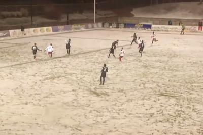American 3rd division soccer game is being played in a blizzard