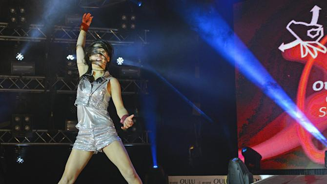 "FILE - In this file photo dated Friday Aug. 29, 2014, showing the winner of the 2014 Air Guitar World Championships, the then 18-year old Nanami ""Seven Seas"" Nagura of Japan, as she performs in Oulu, Finland. What started off as a joke 20-years ago has turned into an annual fest of crazy mime artists pretending to play guitar, competing for the championship title of World Air Guitar champion. (Vesa Ranta/Lehtikuva via AP, FILE)  FINLAND OUT - NO SALES"