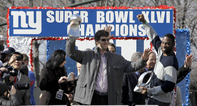 New York Giants quarterback Eli Manning, center, holding the Vince Lombardi Trophy and defensive end Justin Tuck, right, holding the Halas Trophy,  wave to the crowd during a ticker-tape parade celebr