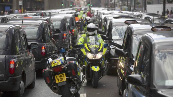 A police motorcyclist manages traffic as taxi drivers demonstrate against Transport for London (TFL) outside the organisation's offices in London