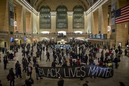 Demonstrators carry a banner through Grand Central Station during a protest against police violence towards minorities in New York