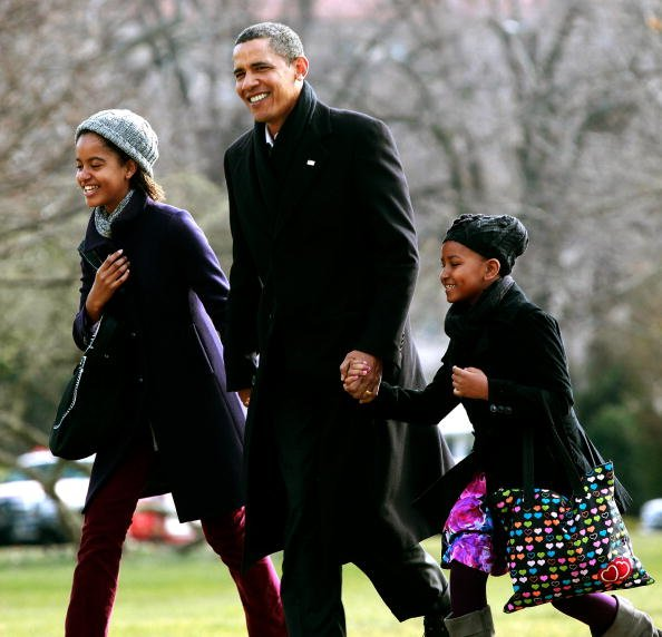 US President Barack Obama (C) walks with his daughters Malia (L) and Sasha (R) after they arrive on the South Lawn of the White House on January 4, 2010 in Washington, DC. President Obama and his fami