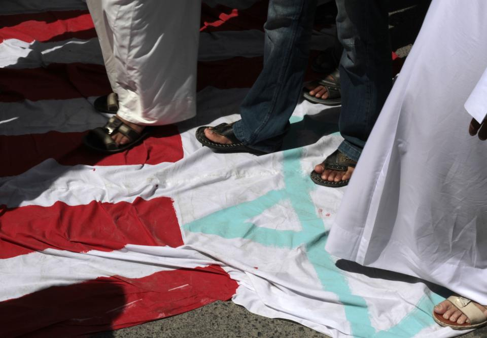 Bahraini worshipers stand on a makeshift flag combining U.S. and Israeli symbols during a protest after midday prayers in Diraz, Bahrain, Friday, Sept. 14, 2012, as part of widespread anger across the Muslim world about a film ridiculing Islam's Prophet Muhammad. (AP Photo/Hasan Jamali)