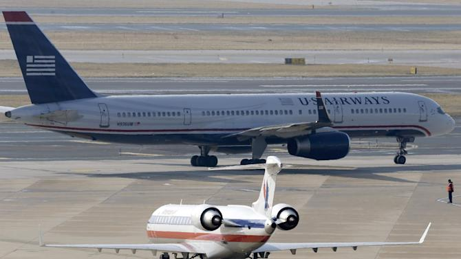 An American Airlines jet taxis near a US Airways jet at the Philadelphia International Airport, Thursday, Feb. 14, 2013, in Philadelphia. The merger of US Airways and American Airlines has given birth to a mega airline with more passengers than any other in the world.  (AP Photo/Matt Rourke)
