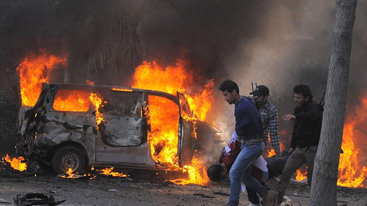 This photo released by the Syrian official news agency SANA, shows Syrian security agents carrying a body following a huge explosion that shook central Damascus, Syria, Thursday, Feb. 21, 2013. A car bomb shook central Damascus on Thursday, exploding near the headquarters of the ruling Baath party and the Russian Embassy, eyewitnesses and opposition activists said. (AP Photo/SANA)
