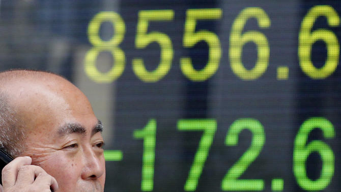 A man speaks on a mobile phone in front of an electronic stock indicator in Tokyo Wednesday, May 23, 2012. Japan's Nikkei 225 index fell 1.98 percent to 8,556.60 as a report that Greece is considering preparations to leave the euro common currency sent Asian stock markets lower Wednesday. (AP Photo/Shizuo Kambayashi)