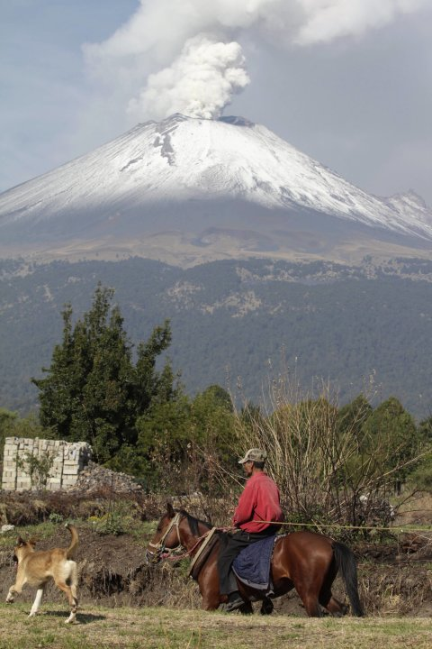 A farmer rides his horse as the snow-covered Popocatepetl volcano spews a cloud of steam high into the air in Puebla