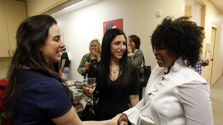 (l-r) Dr. Pari Ghodsi, Dr Roshini Gandhi Mirchandani, and Helen Zimba at the Grand Opening of the new AHF Magic Johnson Healthcare Center in Dallas, Tex. Monday, December 3, 2012 in Fort Worth, Texas. (Richard W. Rodriguez /AP Images for AIDS Healthcare Foundation)