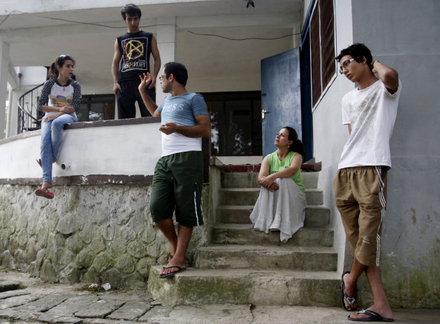 In this photo taken June 28, 2012, asylum seekers, from left to right, Soudeh Mohammadpour, her brother Mehran, Saad Abdul Azm, Zoleikha Golpur and Mojtada Bahadori stand outside their temporary home in Cisarua, West Java, Indonesia. Indonesia became a major transit point for thousands of asylum seekers from various countries who is trying to illegally enter New Zealand and Australia. (AP Photo/Achmad Ibrahim)