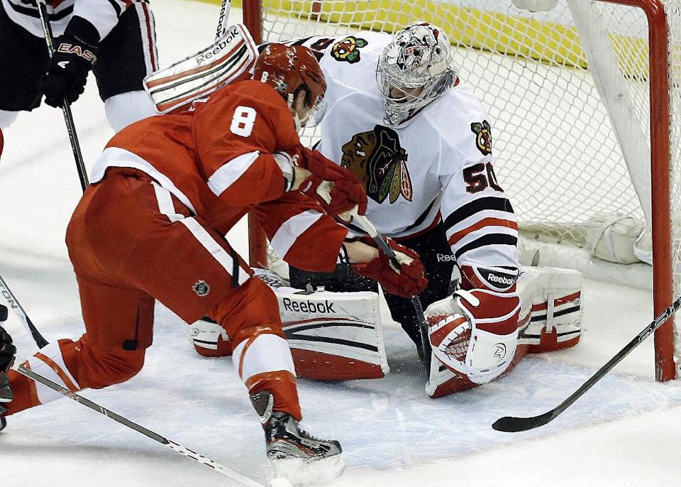 Chicago Blackhawks goalie Corey Crawford (50) stops a shot by Detroit Red Wings left wing Justin Abdelkader (8) during the second period in Game 4 of the Western Conference semifinals in the NHL hockey Stanley Cup playoffs in Detroit, Thursday, May 23, 2013. (AP Photo/Paul Sancya)