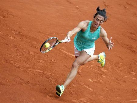 Francesca Schiavone of Italy plays a shot to Svetlana Kuznetsova of Russia during their women's singles match at the French Open tennis tournament at the Roland Garros stadium in Paris