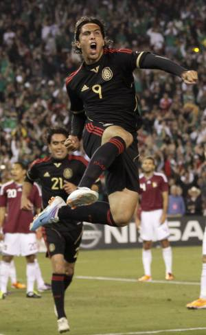 Mexico's Aldo De Nigris jumps after scoring against Venezuela in the second half during their friendly soccer game  Tuesday, March 29, 2011, in San Diego. Behind, Mexico's Edgar Duenas looks on.  (AP Photo/Gregory Bull)
