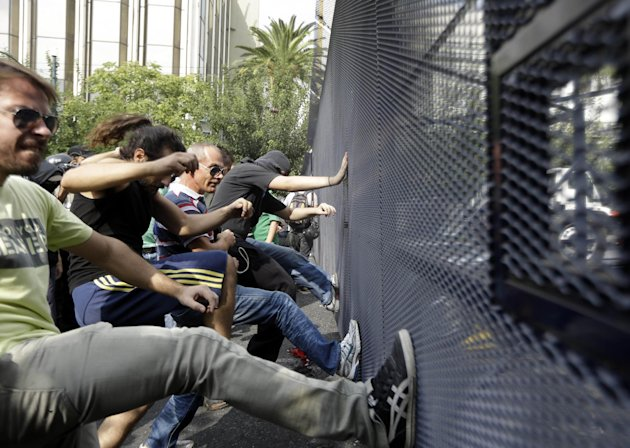 FILE - This Oct. 9, 2012 file photo shows protesters kicking a police barrier during a protest in front of the parliament in Athens. Europe is struggling to control a debt crisis, save the euro currency and stop a repeat of the 2008 financial crisis that sent the world spinning into recession. The continents troubles are the No. 1 threat to the fragile U.S. economy. If the crisis spreads to the U.S., Americans could find it harder to get loans and the country could slip back into recession. (AP Photo/Lefteris Pitarakis, File)