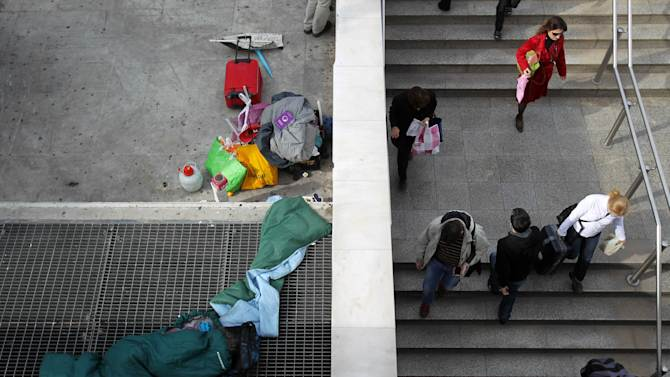 A homeless person sleeps on a metro ventilation grill as commuters enter Syntagma station in Athens, Monday, Nov. 12, 2012. Greek lawmakers approved the country's 2013 austerity budget early Monday, an essential step in Greece's efforts to persuade its international creditors to unblock a vital rescue loan installment without which the country will go bankrupt. (AP Photo/Thanassis Stavrakis)