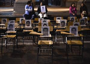 Chairs with portraits of missing students are seen …