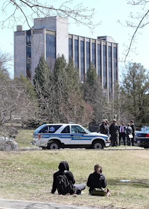 University of Rhode Island students, foreground, watch as State police and local police stand outside Chafee Hall, background, on the campus after the school ordered a lockdown of the campus in South Kingstown, R.I., Thursday, April 4, 2013. The school ended the lockdown after about 2½ hours, and said despite reports of an active shooter on the campus, an investigation revealed there was no gun or active shooter at any time. (AP Photo/Stew Milne)