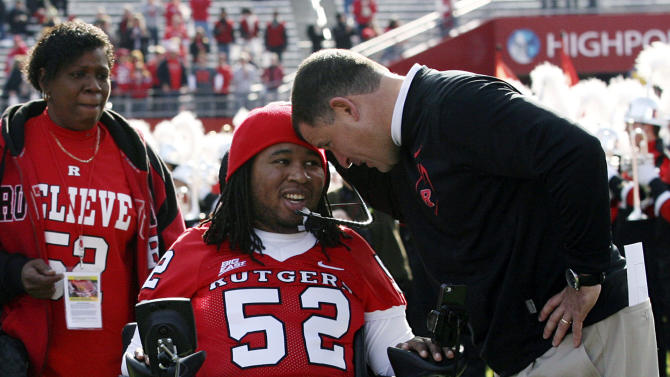 FILE - In this Nov. 19, 2011 file photo, paralyzed former Rutgers football player Eric LeGrand, center, is greeted by coach Greg Schiano, right, before an NCAA college football game against Cincinnati in Piscataway, N.J. Eric's mother, Karen LeGrand, looks on at left. LeGrand has been signed by the Tampa Bay Buccaneers. LeGrand broke two vertebrae and suffered a serious spinal cord injury on Oct. 16, 2010 during a kickoff return against Army. His coach at Rutgers then,  now is coach of the Bucs. (AP Photo/Home News Tribune, Mark R. Sullivan)  NEWARK OUT;  NO SALES