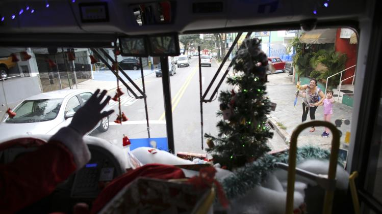 "Bus driver Edilson, also known as ""Fumassa"", greets a mother with her daughter as he wears a Santa Claus outfit inside an urban bus decorated with Christmas motives in Santo Andre"