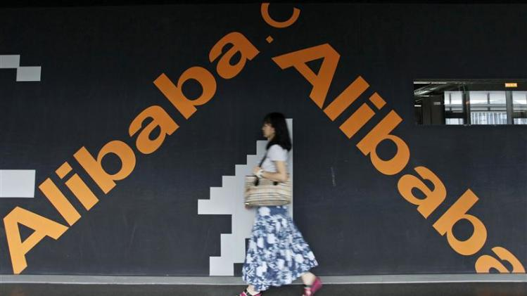 An employee walks past a wall painted with logo of Alibaba (China) Technology Co. Ltd at its headquarters office on the outskirts of Hangzhou