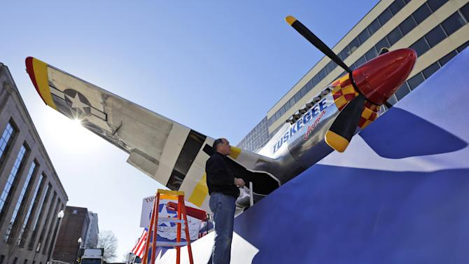 Kevin Tamai with Hargrove Inc., works on a plane on the Tuskegee Airmen float prepared for the 57th Presidential Inaugural Parade, Sunday, Jan. 20, 2013 in Washington. Thousands are planning to march in the 57th Presidential Inauguration parade after the ceremonial swearing-in of President Barack Obama on Monday. (AP Photo/Alex Brandon)