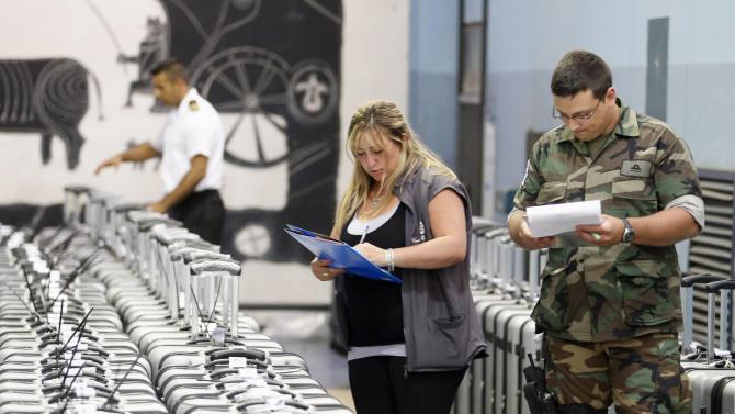 Electoral officers and soldiers check cases containing ballot boxes in an abandoned airport, in the outskirts of Montevideo