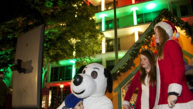 """Snoopy greets children at the """"Snoopy House"""" display that Jim Jordan started 44 years ago, Tuesday, Dec. 13, 2011, on the lawn outside City Hall in Costa Mesa, Calif. as Santa's elves Tori Harris, Kelly O'Leary, right, and Tori Harris look on. The city of Costa Mesa offered to host the massive, animated display of Charles Schulz's """"Peanuts"""" Christmas characters after Jordan lost the home where the tradition was born and flourished to foreclosure. The move saved a wildly popular Christmas display that Jordan says draws 80,000 people _ including busloads of visitors, school groups and lines of children waiting to see Santa. (AP Photo/Damian Dovarganes)"""