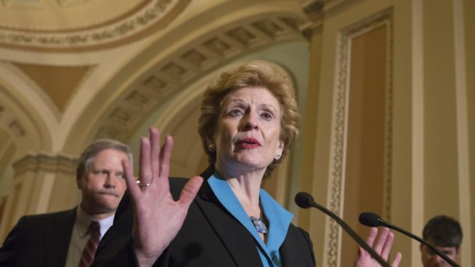 Sen. Debbie Stabenow, D-Mich., chairwoman of the Senate Agriculture Committee, speaks to reporters as the Senate votes on a farm bill that sets policy for farm subsidies, food stamps and other farm and food aid programs for the next five years, at the Capitol in Washington, Monday, June 10, 2013. At rear is Sen. John Hoeven, R-ND. Officially known as the Agriculture Reform, Food and Jobs Act of 2013, the agriculture policy measure would cost taxpayers $100 billion annually with the bulk of that amount allocated to the federal food stamp program which helps low-income families buy food.  (AP Photo/J. Scott Applewhite)