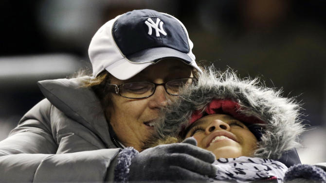 A woman sits with a young girl while they watch a baseball game between the New York Yankees and the Boston Red Sox at Yankee Stadium in New York, Wednesday, April 3, 2013. (AP Photo/Kathy Willens)