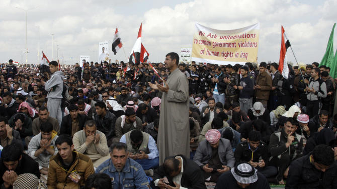 Iraqis perform the Friday noon prayer, the highlight of the religious week, on the highway, which links Iraq with Jordan, during a protest in Fallujah, 40 miles (65 kilometers) west of Baghdad, Iraq, Friday, Feb. 1, 2013. Tens of thousands of Sunni protesters blocked a major highway in western Iraq on Friday, as an al-Qaida-affiliated group called on Sunnis to take up arms against the Shiite-led government. (AP Photo/ Khalid Mohammed)
