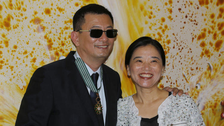 Hong Kong director Wong Kar-wai, left, and his wife Esther smile after he received the Commandeur des Arts et Lettres from French Foreign Minister Laurent Fabius, in Hong Kong Sunday, May 5, 2013. Wong has been given France's highest cultural honor. (AP Photo/Vincent Yu)