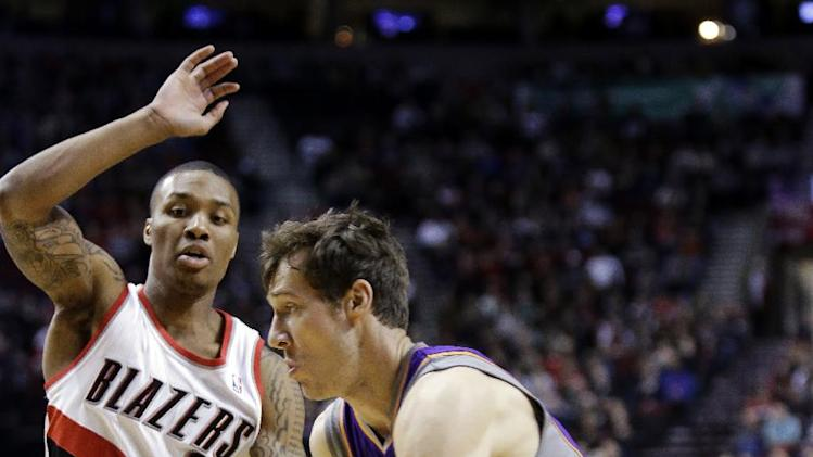 Phoenix Suns guard Goran Dragic, right, of Slovenia, drives on Portland Trail Blazers guard Damian Lillard during the first quarter of an NBA basketball game in Portland, Ore., Tuesday, Feb. 19, 2013. (AP Photo/Don Ryan)