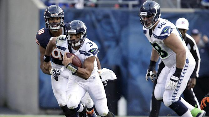 Seattle Seahawks quarterback Russell Wilson (3) rushes past Chicago Bears defensive end Corey Wootton (98) during the second half of an NFL football game in Chicago, Sunday, Dec. 2, 2012. (AP Photo/Nam Y. Huh)