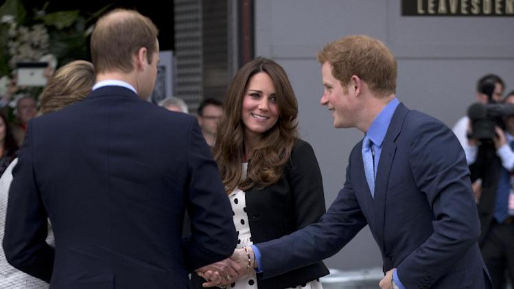"Britain's Kate the Duchess of Cambridge stands with her husband Prince William, left, and his brother Prince Harry, right, as they are greeted upon their arrival to attend the inauguration of ""Warner Bros. Studios Leavesden"" near Watford, approximately 18 miles north west of central London, Friday, April 26, 2013.  As well as attending the inauguration Friday at the former World War II airfield site, the royals will undertake a tour of Warner Bros. ""Studio Tour London - The Making of Harry Potter"", where they will view props, costumes and models from the Harry Potter film series. (AP Photo/Matt Dunham)"