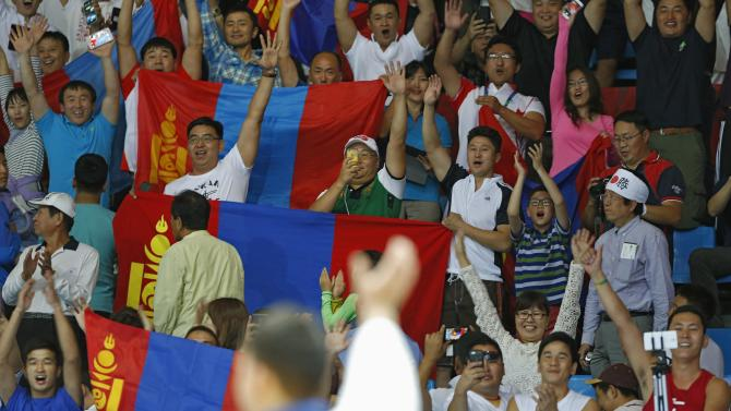 Mongolia's Naidan waves to the crowd after winning gold in the men's -100 kg gold medal judo contest during the 17th Asian Games in Incheon