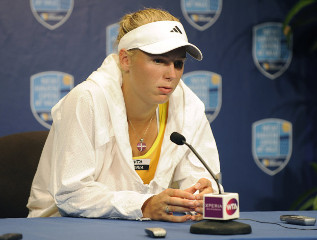 Caroline Wozniacki, of Denmark, speaks with reporters after retiring from her semifinal match, after losing the first set 7-5, against Maria Kirilenko, of Russia, at the New Haven Open tennis tournament in New Haven, Conn., on Friday, Aug. 24, 2012. A right knee injury suffered in the quarterfinals forced the retirement.