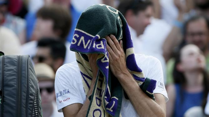 James Ward of Britain wipes his face during a break between games of his match against Vasek Pospisil of Canada at the Wimbledon Tennis Championships in London