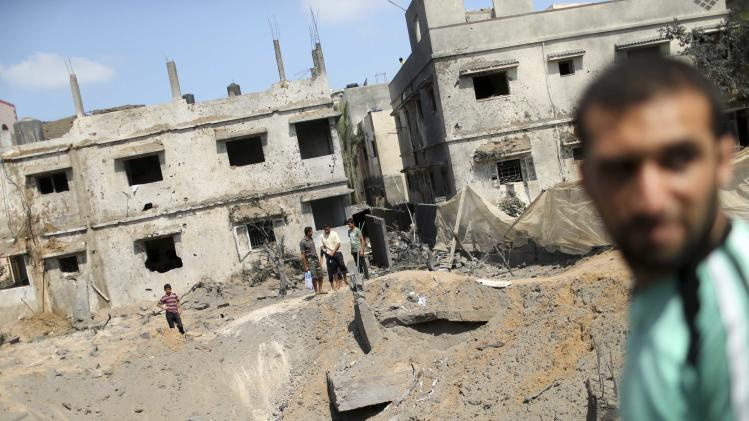Palestinians gather around the remains of a house, which witnesses said was destroyed in an Israeli air strike, in Gaza City