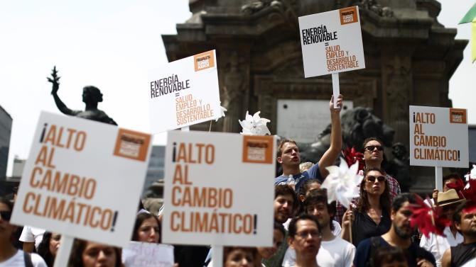 People hold posters during a Climate Change march to demand politicians take tougher action to protect the climate at Angel de la Independencia monument in Mexico City