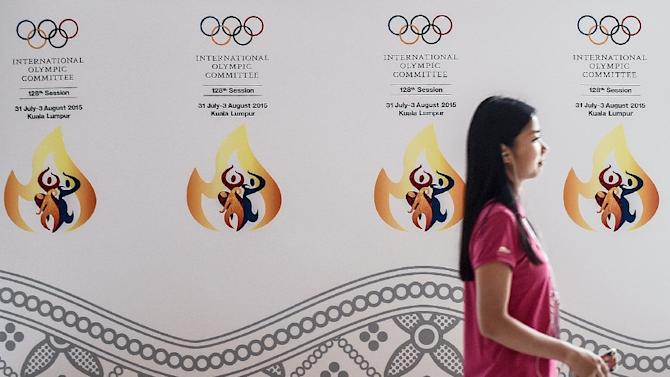 A woman walks past a banner for International Olympic Committee meeting  at a convention centre in Kuala Lumpur on July 28, 2015